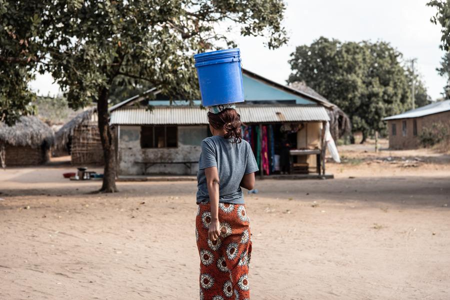 Frau trägt Wasser am Kopf